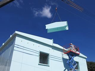 発電機用大型防音カバーの屋根パネルを吊り上げた写真